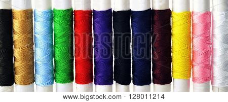 different spools of color  threads on white