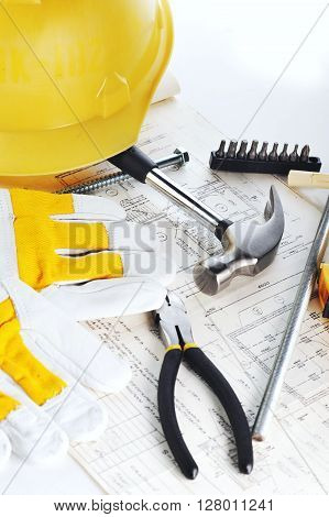 Yellow hardhat gloves and hammer on drawings