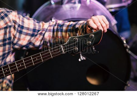 Young man tuning a electric guitar. Selective focus on the hand. Unrecognizable guitarist tuning guitar on concert  stage in sound recording studio.