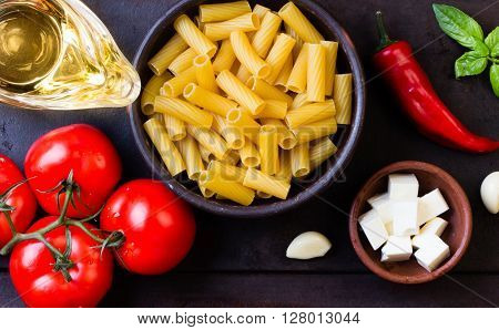 Pasta. Ingredients for italian food - salad wish pasta and vegetables - dry penne , olive oil, basil, garlic, tomatoes, basil, black pepper, cheese. Top view