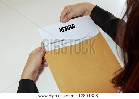 Businesswoman opening resume in letter envelope concept