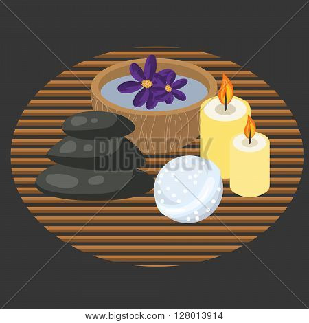 Spa procedure accessories on makisu mat. Spa massage pebbles, candles, bath bomb and aroma water in bowl.