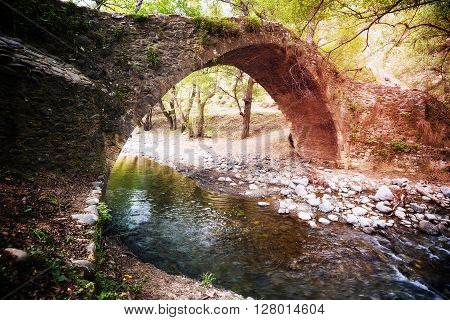 Medieval Venetian bridge over a small river in the morning sun. Spring on Cyprus.