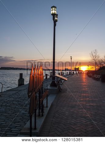 Rising sun beginning to brighten Harborwalk along Boston harbor