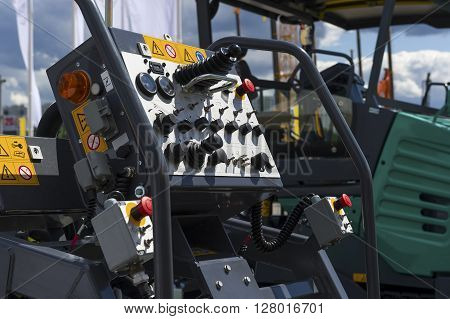 Control panel of asphalt paving machine, heavy industry, dashboard unit with buttons, levers, toggle switches, knobs, signal lights, sensors, indicators and handles, road construction machines on background