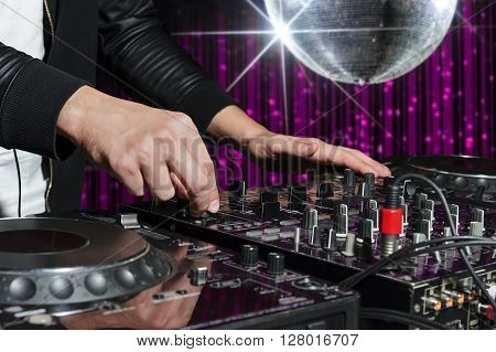 DJ at nightclub party playing on sound mixer, striped pink interior and silver disco ball with star on background, nightlife entertainment industry