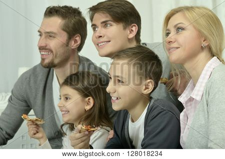 portrait of happy family at home with pizza