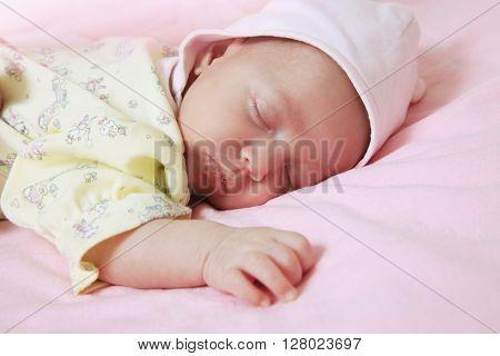 New born baby girl peacefully sleeping .