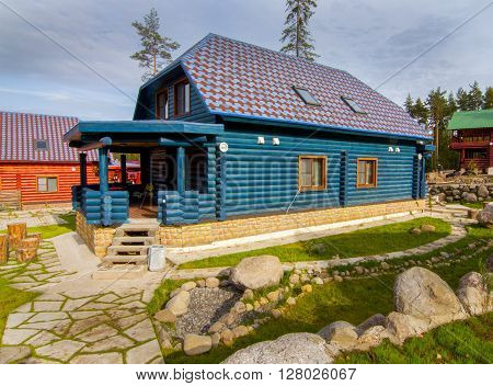 a house made of wooden logs in the village against the blue sky