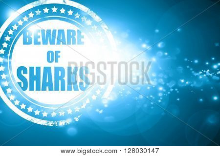Blue stamp on a glittering background: Beware of sharks sign
