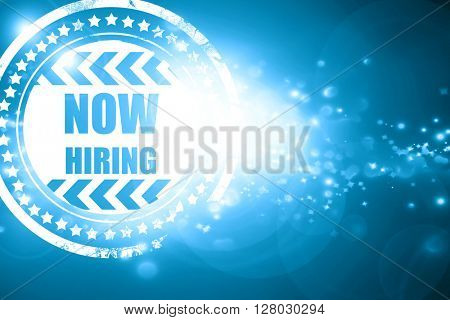 Blue stamp on a glittering background: Now hiring sign