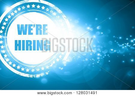 Blue stamp on a glittering background: We are hiring sign