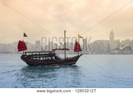 HONG KONG - FEBRUARY 25: The junk boat in Victoria harbor on February 25 2013 in Hong Kong. A red chinese traditional junk boat Aqua Luna is one of famous tourist attraction