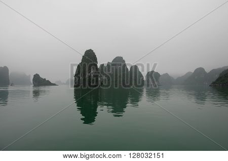 Early morning fog on limestone mountains Halong bay Vietnam