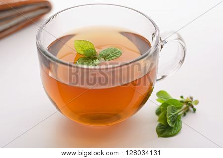 Cup of tea with lemongrass leaves and the leaves are on the table, natural light, bokeh.
