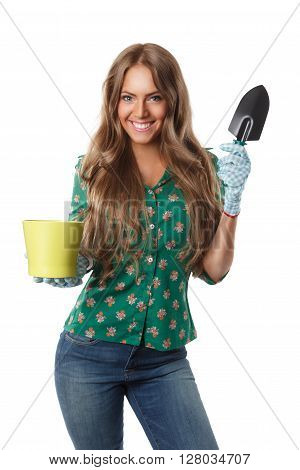 Beautiful gardening housewife holding a pot and a mini shover