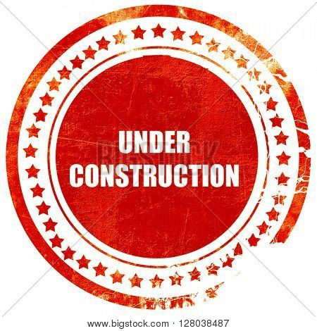 Under construction sign, grunge red rubber stamp on a solid whit