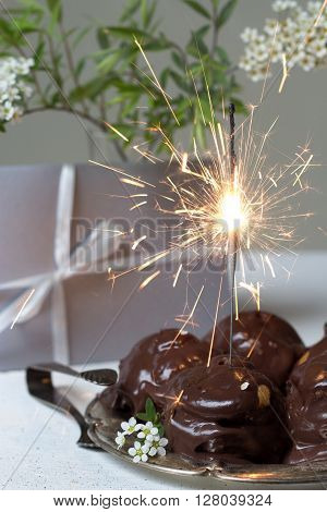gift, tasty cream puffs in chocolate sauce and sparklers