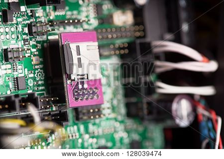 Green system board with microchips and transistors. Microchips are shown in different sizes. Close up photo.