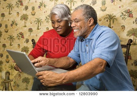 Portrait of mature African American couple looking at laptop in home.