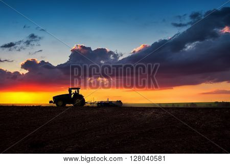 Farmer in tractor preparing land with seedbed cultivator sunset shot