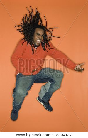 African-American mid-adult man on orange background jumping while playing air guitar.