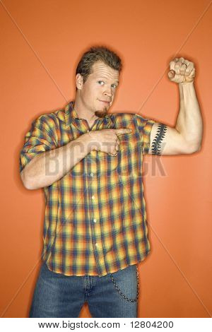Portrait of adult Caucasian man on orange background flexing and showing off his arm muscle.