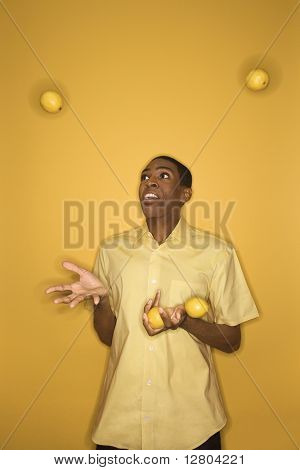 Young African-American man juggling lemons on yellow background.