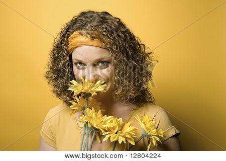 Retrato de jovem adulto branca sobre fundo amarelo, segurando e buquê de flores de cheiro