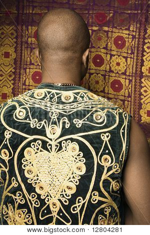 Rear view portrait of African-American mid-adult man wearing embroidered African vest.