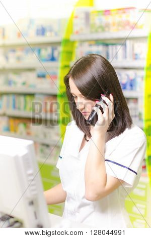 Young pharmacist woman having a phone call while doing by computer. Pharmaceutical background. Drugstore. Pills and medicine.