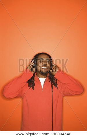 African-American mid-adult man listening to headphones wearing orange clothing on orange background.