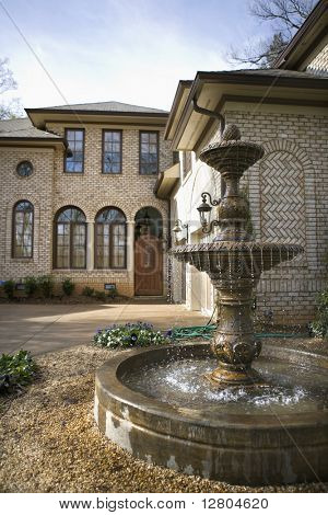 Outdoor front view of affluent home with fountain.