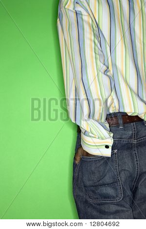 Back view torso of African-American teen boy with hand in back pocket of jeans standing against green background.