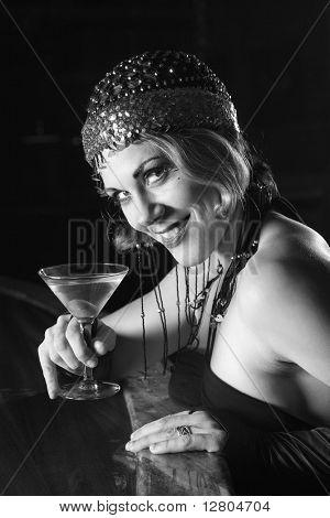 Caucasian prime adult retro female sitting at bar with martini looking at viewer.