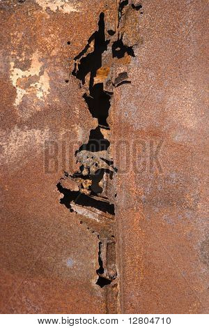 Close-up of old rusted car with crack down the middle.