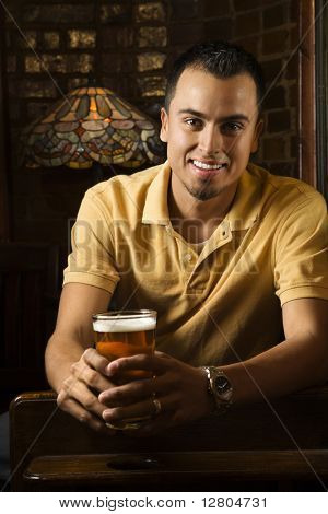 Portrait of smiling young Hispanic man holding beer in pub.