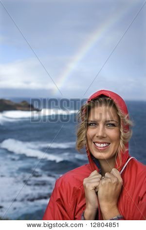 Caucasian mid-adult woman in red raincoat standing by ocean with rainbow in background in Maui, Hawaii.