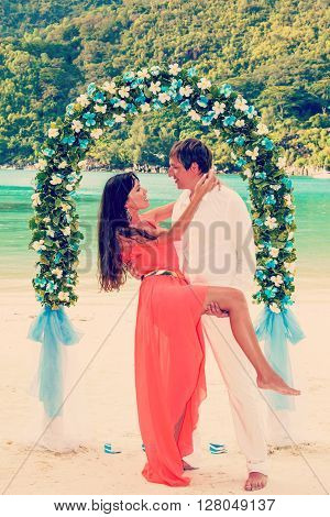 young newly married couple and wedding ceremony on the beach, the details of design, bouquet of frangipani, Seychelles