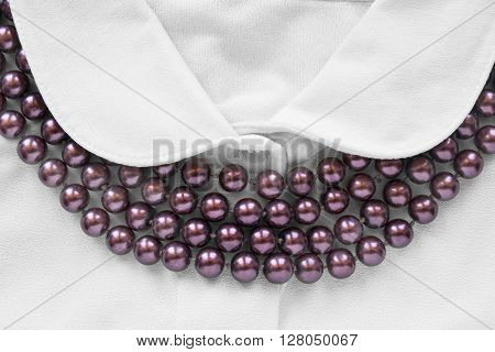 Strings of purple beads on white blouse closeup as a background