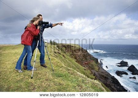 Caucasian mid-adult couple pointing and looking through camera from cliff overlooking the ocean in Maui, Hawaii.