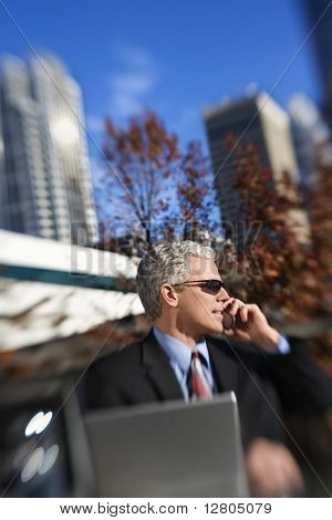 Prime adult Caucasian man in suit sitting at patio table outside with laptop talking on cellphone wearing sunglasses with buildings in background.