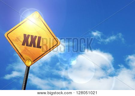 Yellow road sign with a blue sky and white clouds: xxl sign back