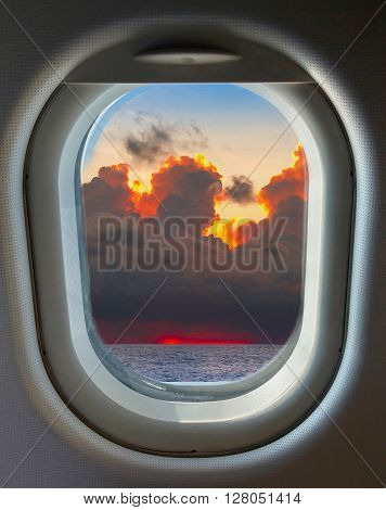 porthole and top view from the airplane on the blue sky and clouds