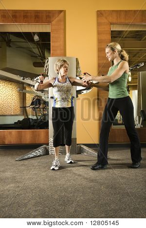 Prime adult Caucasian female helping mature adult Caucasian female use exercise equipment at gym.