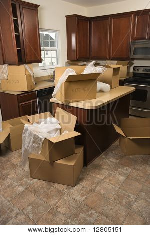 Cardboard moving boxes with bubble wrap in kitchen.
