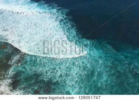 Ocean and rip curl view from abrupt cliff coast, look down from the height, Bali sea landscape, Blue waves near the tropical beach, blue waves for surfing, Indonesia, island Bali, Indonesia