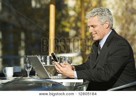 Profile of smiling prime adult Caucasian man in suit sitting at patio table outside with laptop and dialing cellphone.