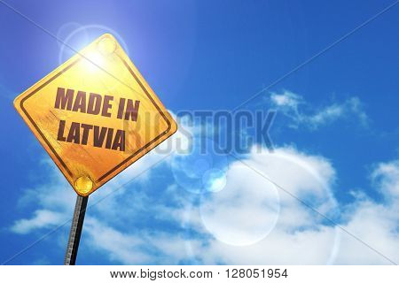 Yellow road sign with a blue sky and white clouds: Made in latvia