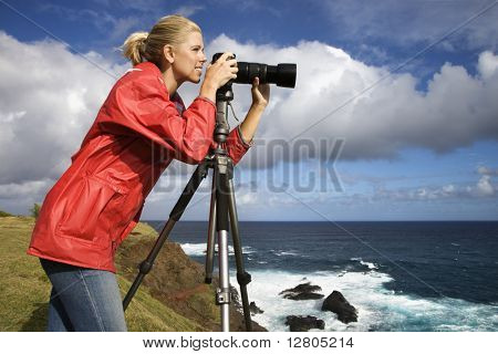 Caucasian mid-adult woman looking through camera on tripod on cliff overlooking ocean in Maui, Hawaii.